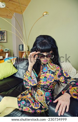 Groovy woman in 1960s fashion looking over sunglasses - stock photo