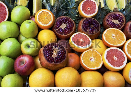 groseries shelf with fresh tropic fruits oranges, pineapple slices, apples and pommegranates - stock photo