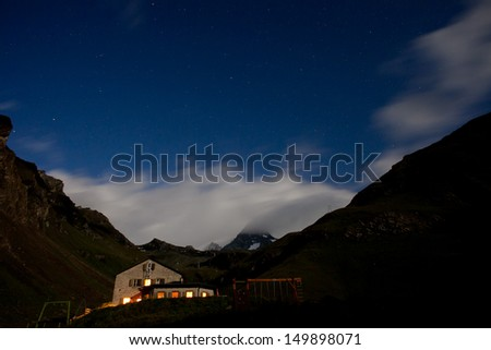 Grossglockner the highest peak in Austrian alps at night covered by clouds with stary sky - stock photo
