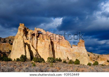 Grosvenors Arch in Utah with approaching dark blue and grey rain and snow clouds