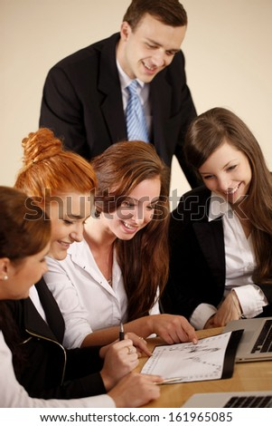 Grou of young businesswoman and one man analyzing a diagram in the office with smile. - stock photo