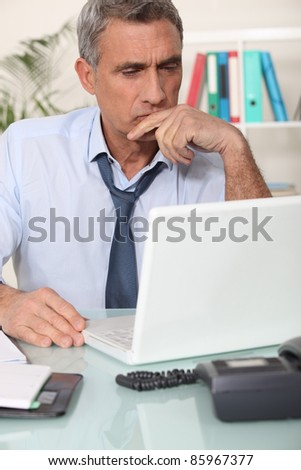 Grouchy man reading an email - stock photo