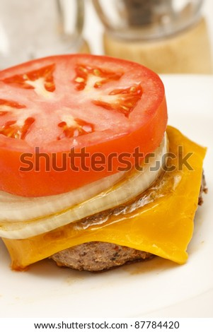 Ground Beef patty, onion and tomato slice and melted cheese ready for a bun