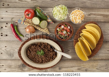 Ground beef tacos, preparation ingredients set in a wooden table - stock photo