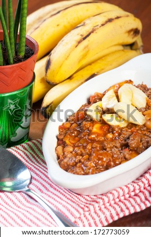ground beef with beans in tomato sauce and fresh banana - stock photo