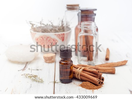 ground cinnamon, essential oil and cinnamon sticks cinnamon on a white background - stock photo