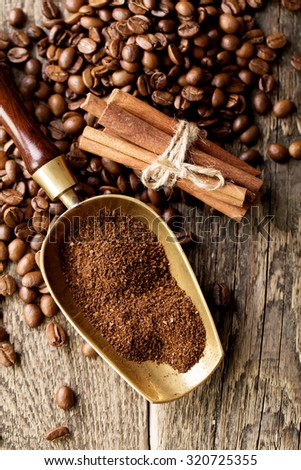 ground coffee in scoop and coffee beans on a wooden background