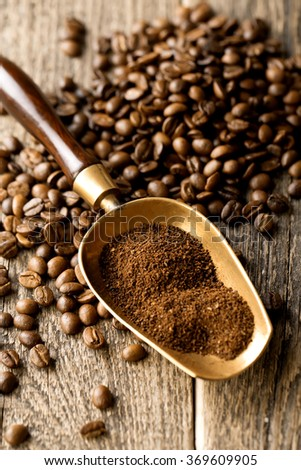 ground coffee in scoop and coffee beans on a wooden background - stock photo