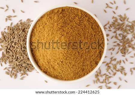 Ground cumin in a bowl  and whole cumin - stock photo