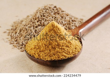 Ground cumin in a spoon and Pile of cumin seeds - stock photo