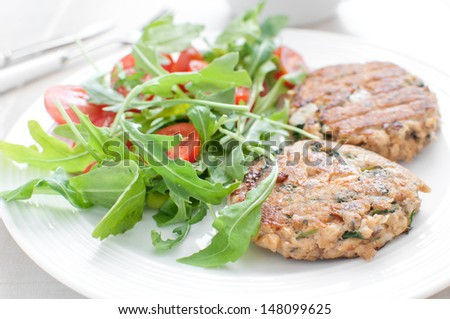 Ground fish patty with arugula tomato healthy salad - stock photo