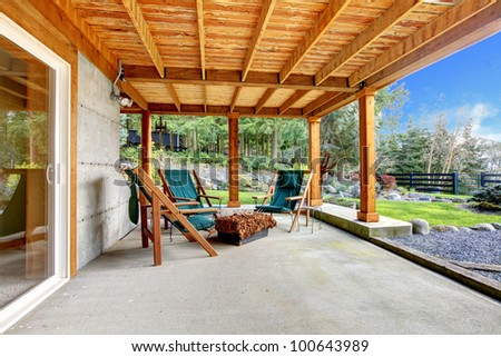 Ground level deck with chairs and door with wood ceiling. - stock photo