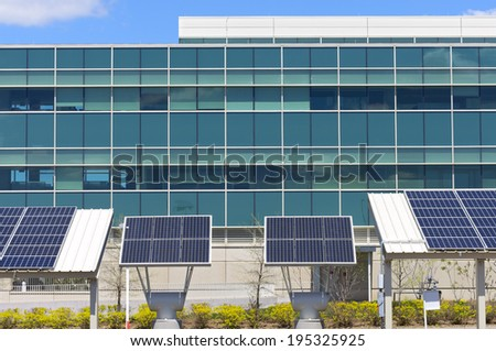Ground level solar panel arrays in front of modern office building - stock photo
