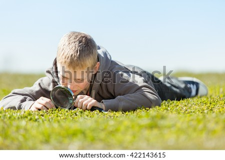 Ground level view on cute blond boy in gray sweater with curious expression using magnifying glass over field of grass - stock photo
