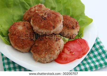 Ground meat fried in  breadcrumbs. Fried cutlet, tomato and lettuce on a plate. - stock photo
