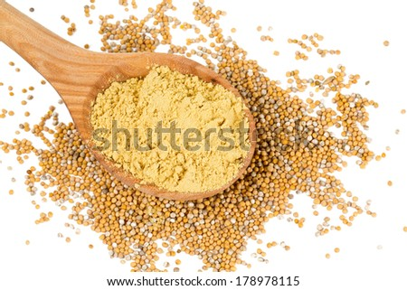 ground mustard in a wooden spoon over mustard seeds