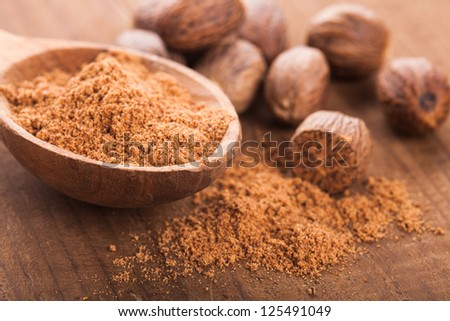 Ground nutmeg spice in the wooden spoon closeup - stock photo