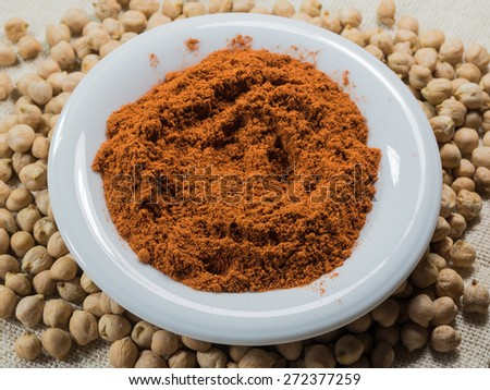 Ground paprika on a white plate and chickpeas on sacking - stock photo