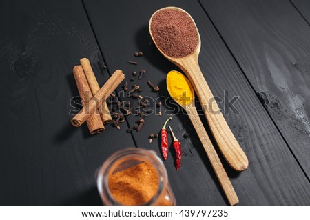 Ground spices in bottles with spon, papper, cinnamon on black wooden background. Close-up - stock photo
