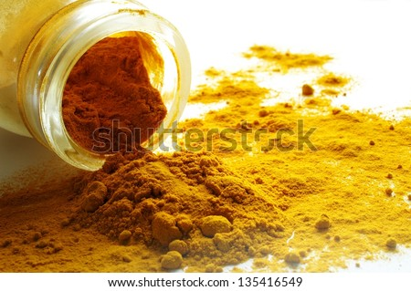 ground turmeric spilling from glass jar - stock photo