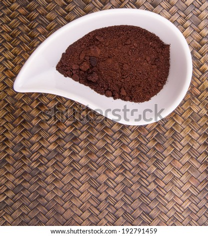 Grounded coffee in a white ceramic container over wicker background