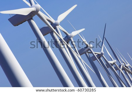 group aligned modern windmills for renewable electric energy production - stock photo