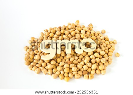 Group chickpeas around wooden letters that read ''GMO '' - stock photo
