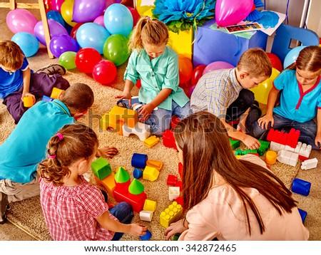 Group children game blocks and balloons on floor in kindergarten . Top view.  - stock photo