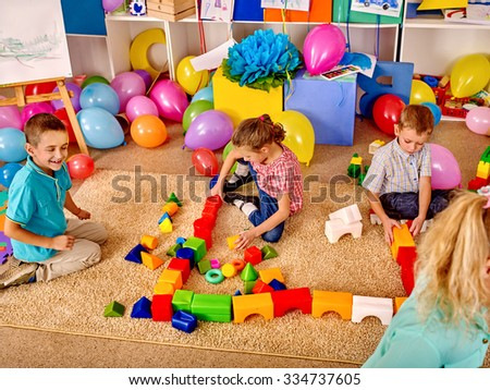 Group children game blocks on carpet floor in kindergarten . Top view. - stock photo