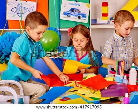 Group children holding colored paper on table in kindergarten . Children together work with paper in art class. - stock photo