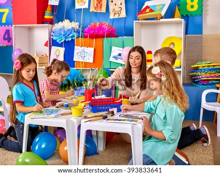 Group children with young teacher woman painting on paper at table  in  art class kindergarten . Creativity training. - stock photo