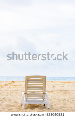 Group deck chairs under an umbrella on a sandy beach sea tropical sunny day