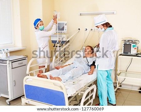 Group doctor treats female patient with stethoscope. - stock photo