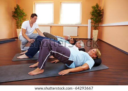 Group doing back exercises in a gym - stock photo