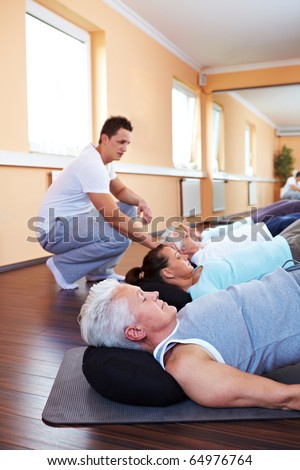 Group doing back exercises in a gym with fitness trainer