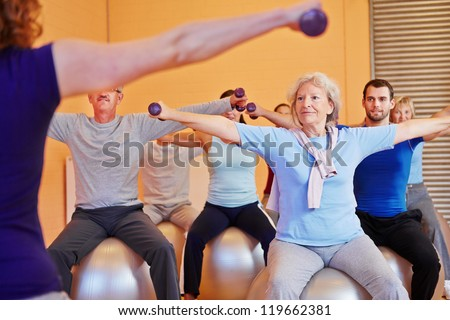 Group doing back training with female fitness instructor in gym - stock photo