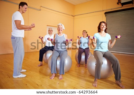 Group doing dumbbell exercises in a gym
