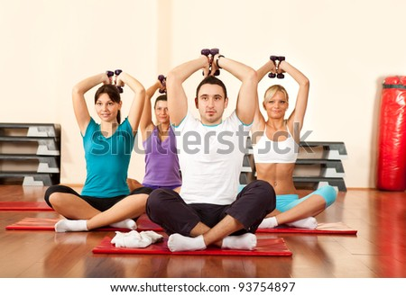 group doing dumbbell exercises in a gym - stock photo