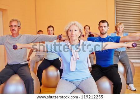 Group doing dumbbell exercises in gym for back training - stock photo