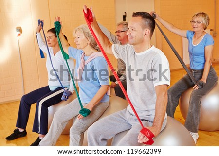 Group doing senior fitness sports with exercise band in gym - stock photo