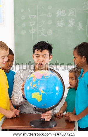 group elementary school students and teacher looking at globe in classroom