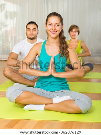 Group enjoying yoga class in sport club - stock photo