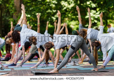 Group free exercise class for people of different age and gender in the city park. International Day of Yoga, summer