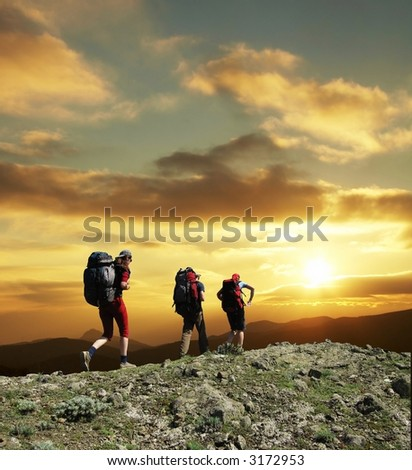 Group going along hill on sunset - stock photo