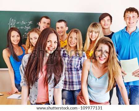 Group happy student near green  blackboard in classroom. - stock photo