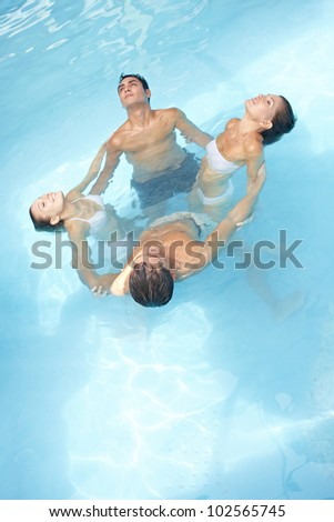 Group in a circle doing water yoga in swimming pool - stock photo