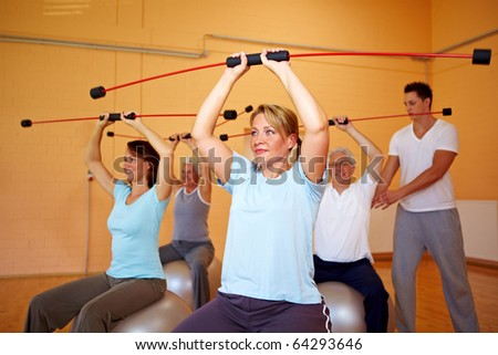 Group in a gym doing fitness exercises with a flexibar