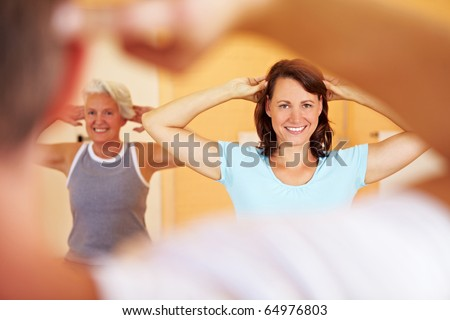 Group in a gym doing gymnastics with a fitness trainer - stock photo