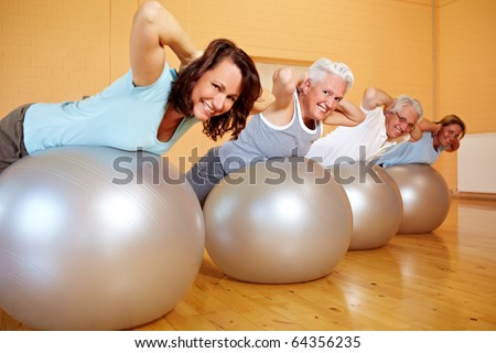 Group in gym doing back exercises on Swiss balls - stock photo