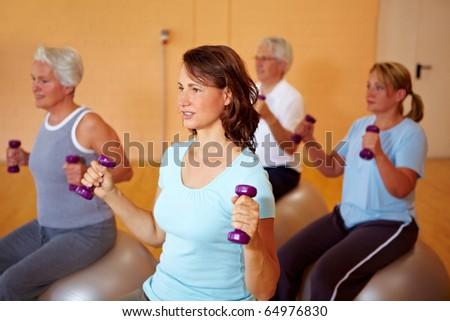 Group in gym doing dumbbell training on Swiss balls - stock photo